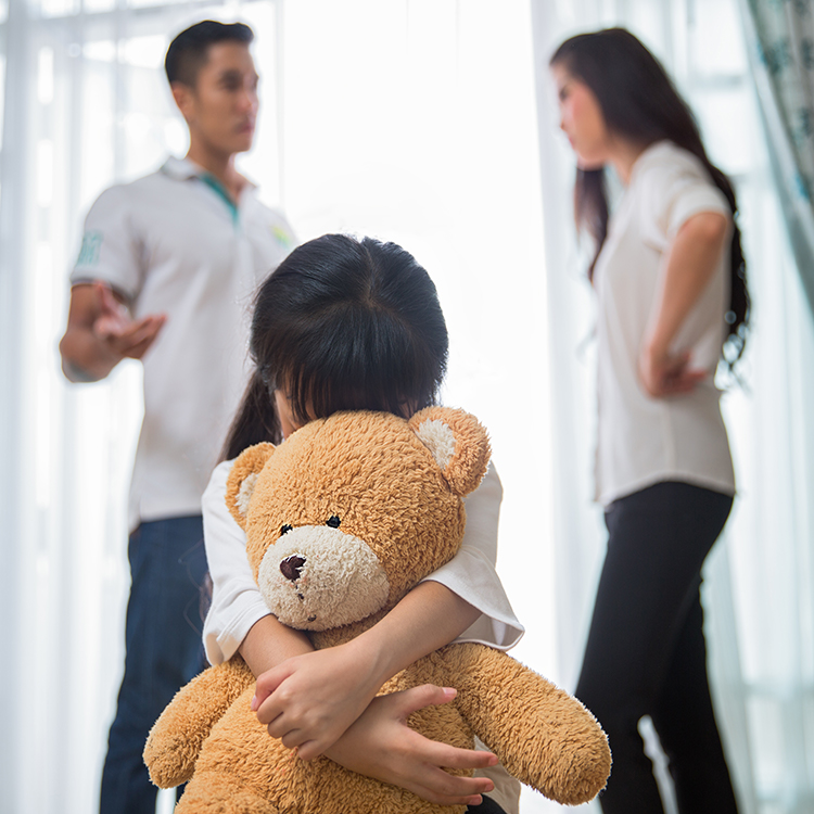 A man and a woman arguing in front of a child while the child holds a teddy bear for comfort